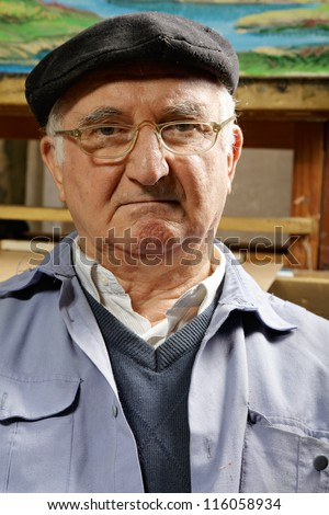 Portrait of artist made in workshop against his painting - stock photo