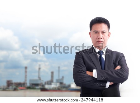 Portrait of asia business man has oil industry background .cross one's arm,Positive emotion - stock photo