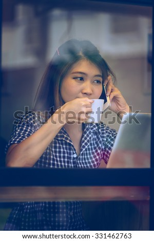 Portrait of asia pretty woman talking on phone while sitting in cafe and enjoying coffee, Vacations concept.