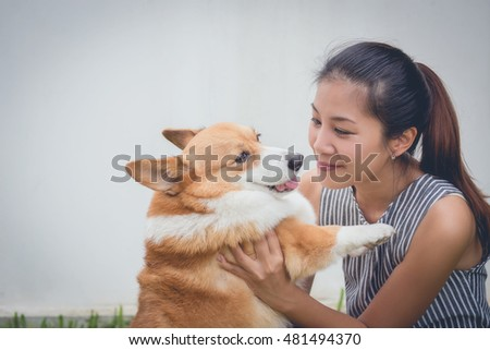 Portrait of asia woman with dog Welsh Corgi Pembroke in garden, white wall background