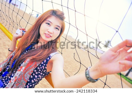 Portrait of Asia young woman near volleyball net on the beach