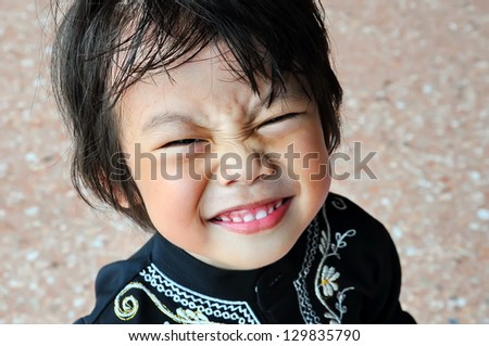 Portrait of asian boy with smile gesture and closed eyes - stock photo