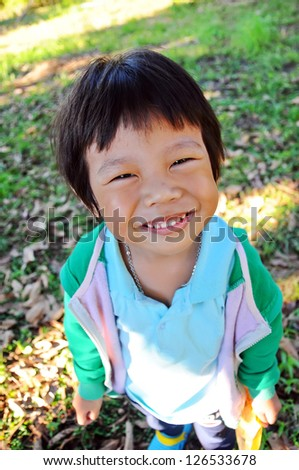 Portrait of asian boy with smile on the grass - stock photo