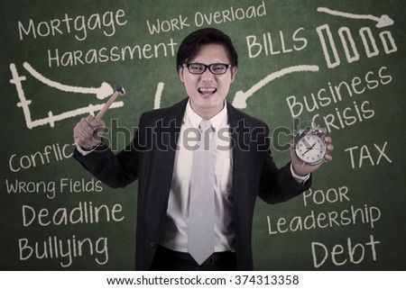 Portrait of asian businessman angry holding hammer and alarm with scribble on the chalkboard - stock photo