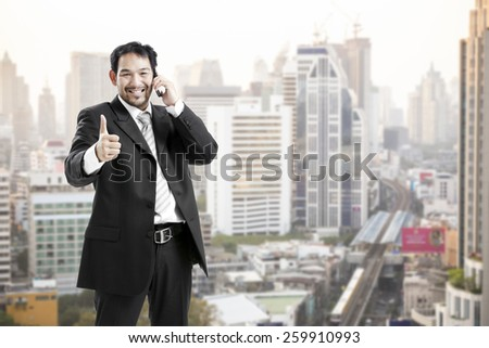 Portrait of asian businessman in suit outdoors,talking on the phone