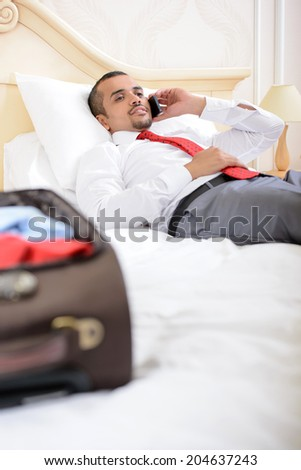 Portrait of Asian businessman with a suitcase lying on the bed and talking on the phone in a hotel room