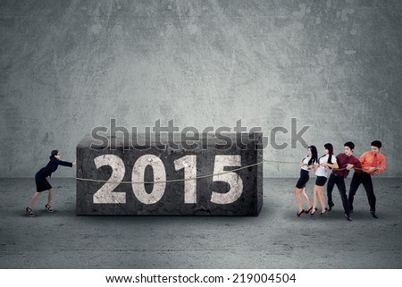 Portrait of asian businesspeople collaborate to move a boulder with a text of 2015 - stock photo