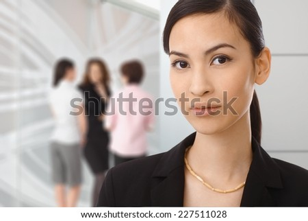Portrait of asian businesswoman at office, colleagues in background.