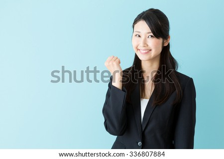 portrait of asian businesswoman isolated on blue background - stock photo