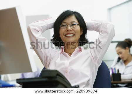 Portrait of Asian businesswoman with arms behind head - stock photo