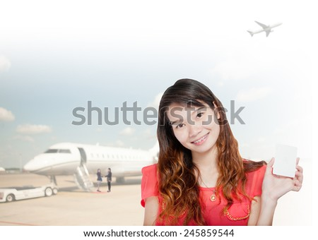 portrait of asian  businesswomen wearing red and hold card has airport background .Mixed Asian / Caucasian businesswoman.Positive emotion - stock photo
