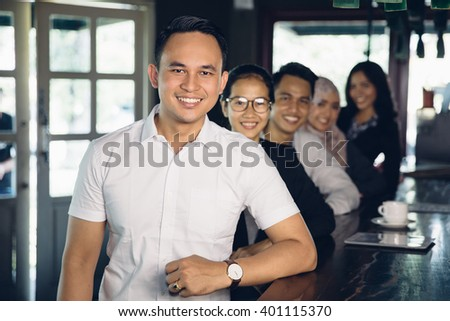 portrait of asian casual businessman leader on the foreground of his team - stock photo