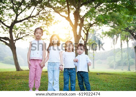 Portrait of Asian children holding hands at park. Little girls and boy having fun outdoors. Morning sun flare background.