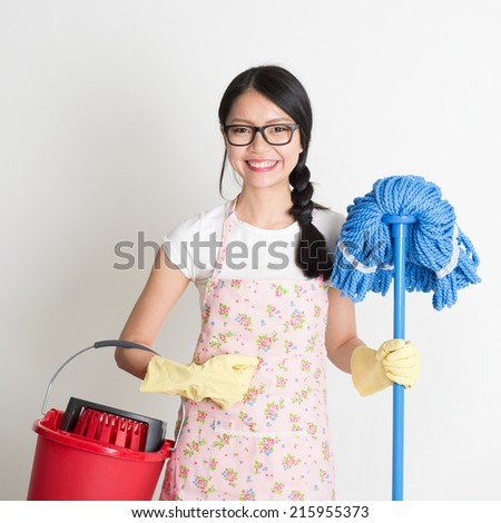 Portrait of Asian Chinese woman housekeeping, holding bucket and mop on plain background.