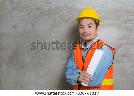 portrait of asian construction technician with concrete wall background