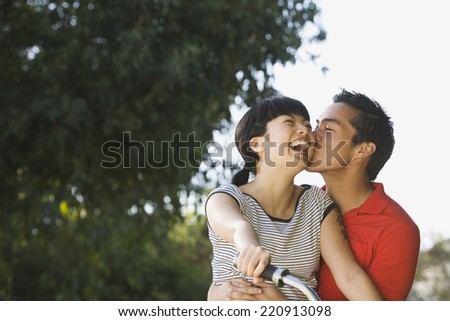 Portrait of Asian couple kissing - stock photo