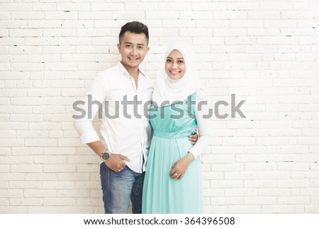 portrait of asian couple standing while embracing each other with copy space on white background - stock photo