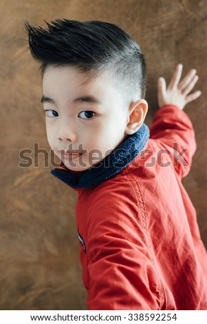 portrait of Asian cute boy over on brown leather background,wear red sweaters