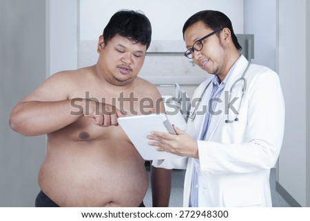 Portrait of asian doctor showing the checkup result to the overweight patient - stock photo