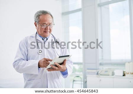 Portrait of Asian doctor using tablet computer