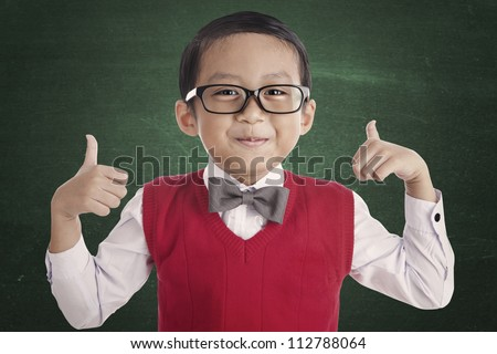 Portrait of asian elementary school student and thumbs-up. shot in the classroom - stock photo
