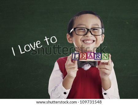 Portrait of asian elementary school student showing LEARN word. shot in class - stock photo