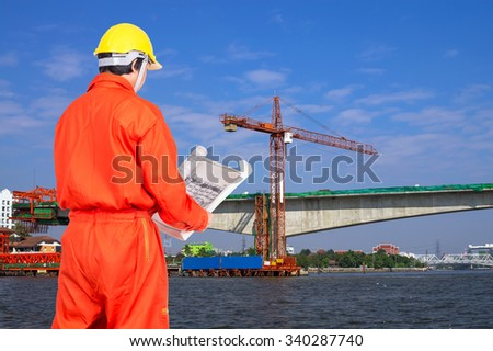 Portrait of Asian engineers looking at the blueprint on construction site worker over the river, industrial construction concept