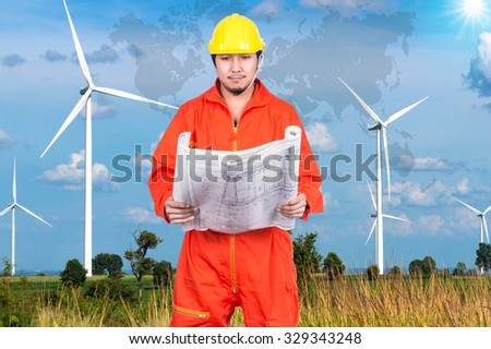 Portrait of Asian engineers looking at the blueprint on Wind turbine power generator with world map, industrial concept, Elements of this image furnished by NASA