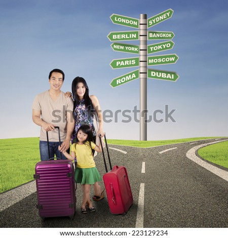 Portrait of asian family carrying luggage and standing on road with signpost of destination choice - stock photo