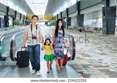 Portrait of asian family carrying luggage and walking in the airport hall for holiday - stock photo
