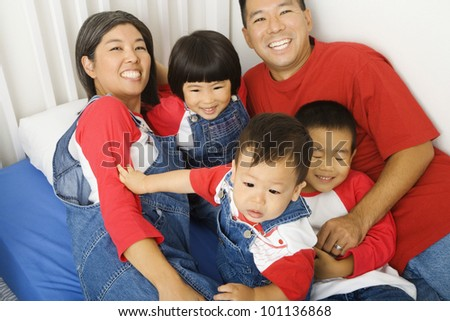 Portrait of Asian family on bed