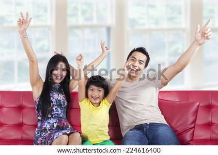 Portrait of asian family sitting on sofa and expressing happy at home - stock photo