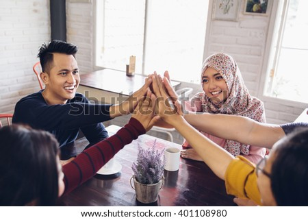 portrait of asian friend giving high five at cafe