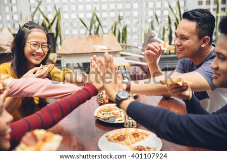 portrait of asian friend giving high five at cafe while having a lunch - stock photo
