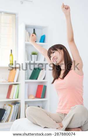 Portrait of Asian girl woke up and stretching arms in the morning. Young woman indoors living lifestyle at home.