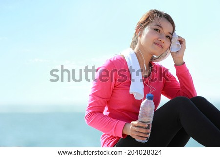 Portrait of asian healthy fitness woman holding a bottle of water while having a break - stock photo