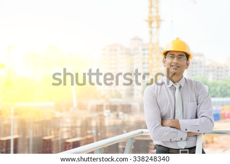 Portrait of Asian Indian male site contractor engineer with hard hat holding blue print paper smiling at construction site, crane with golden sunlight at the background. - stock photo