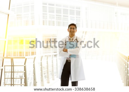 Portrait of Asian Indian medical doctor holding medical report, standing outside hospital building block, beautiful golden sunlight at background.