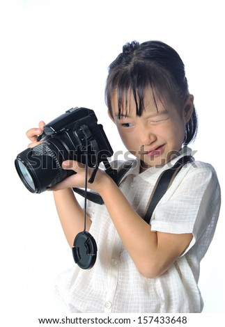 Portrait of asian little girl holding photo camera isolated on white background