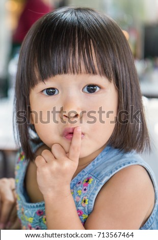 Portrait of Asian little girl say be quiet, small asian girl with one finger on her mouth, close up and explession