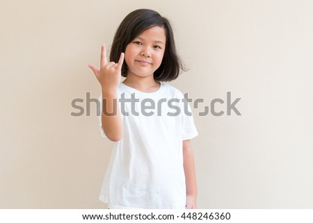 Portrait of asian little girl smiling and show love sign hand. Portrait of asian girl smiling for inspiration concept ideas. Little girl standing front of space background - stock photo