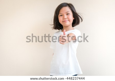 Portrait of asian little girl  smiling and showing thumb up, finger sign. Portrait of asian girl smiling for inspiration concept ideas. - stock photo
