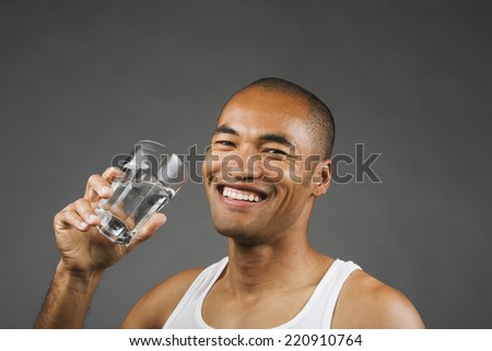 Portrait of Asian man drinking glass of water - stock photo