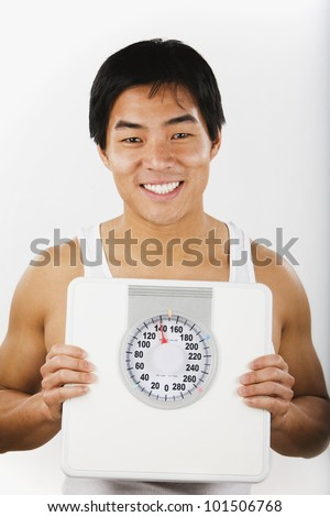 Portrait of Asian man holding bathroom scale