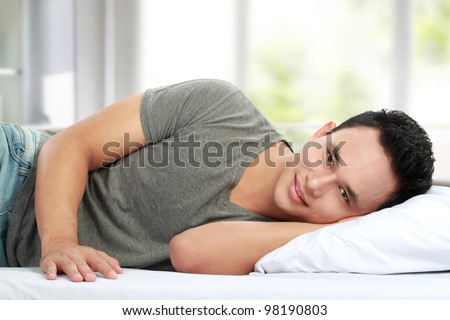 portrait of asian Man lying in bed smiling