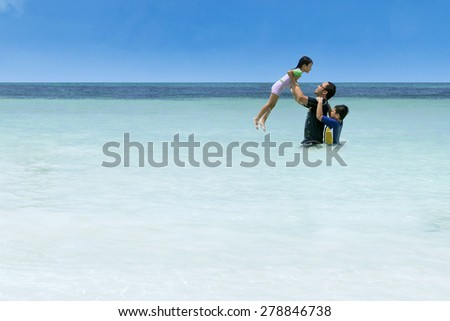 Portrait of asian man playing with his children on the beach - stock photo