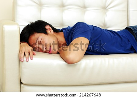 Portrait of asian man sleeping on the sofa - stock photo