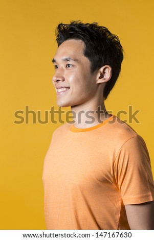 Portrait of Asian man standing against yellow background.