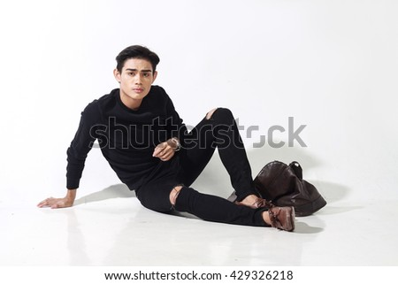 portrait of asian man with his leather bag sitting on white wall