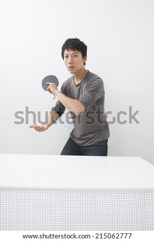 Portrait of Asian mid adult man playing table tennis